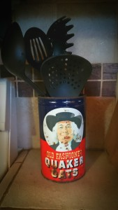 Photo of a vintage Quaker Oats oatmeal tin with large kitchen utensils inside.