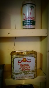 Photo of two vintage spice tins in a vintage yellow spice rack.