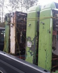 Photo of 4 salvaged vintage gas pumps loaded in the back of a pickup truck.