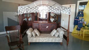 Photo of antique canopy bed frame, settee, dresser, chair, and amiore.
