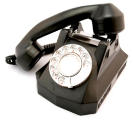 Image of an old black rotary telephone.
