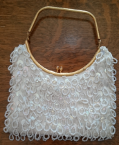 Photo of a vintage white hand beaded hand bag with a gold handle.