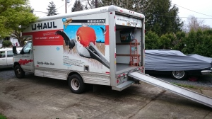 Photo of a 17' U-Haul truck backed into a driveway with the back open and the ramp extended.