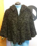 Photo of a vintage black karakul sheep cape on a dress form.