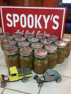 Photo of multiple jars of Spookys Hot Rod Salsa with signage and two vintage toy hot rod cars.